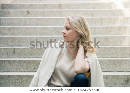portrait of casual brunette woman sitting and holding her neck Stock photo © feedough
