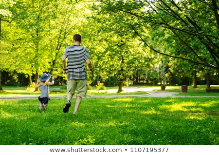 Dad and daughter running through park Stock photo © bluering
