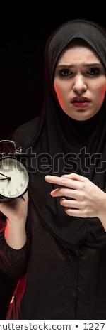 Portrait of beautiful serious scared frightened young muslim woman wearing black hijab holding alarm Stock photo © Traimak