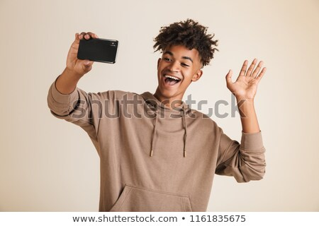 American man dressed in hoodie taking a selfie isolated while waving. Stock photo © deandrobot