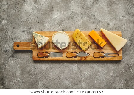 Assortment of various kinds of cheeses served on wooden board with fork and knives Stock photo © dash