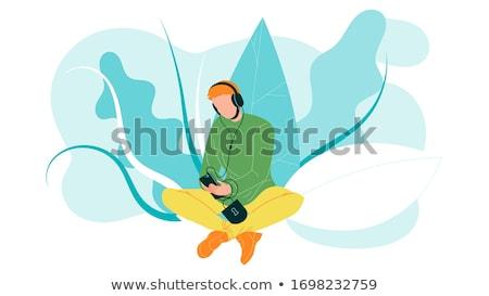 Férfi fülhallgató okostelefon ül fű emberek Stock fotó © dolgachov
