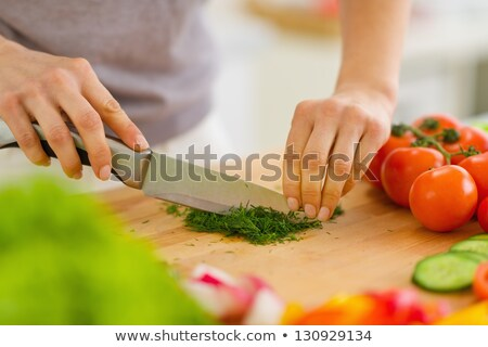 womans hand cutting cucumber with kitchen knife stock photo © andreypopov