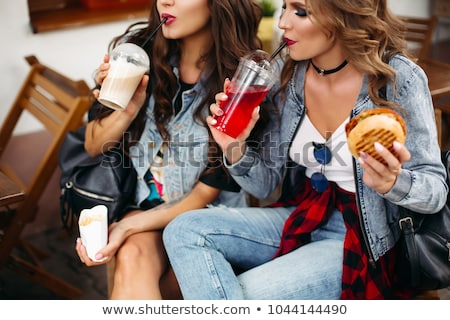 Beautiful girls with make up and hairstyle drinking fizzy drink and eating fast food. Stock photo © studiolucky