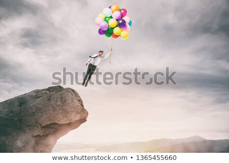 Creative businessman holding colorful balloons flies from the peak of a mountain Stock photo © alphaspirit