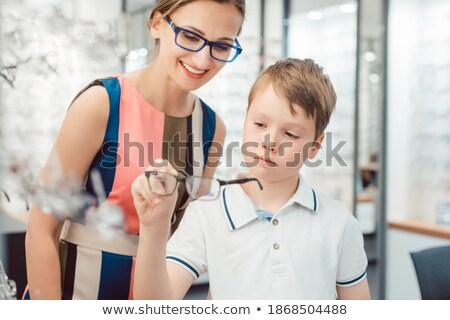 Mother and son looking for new glasses in optometrist store Stock photo © Kzenon