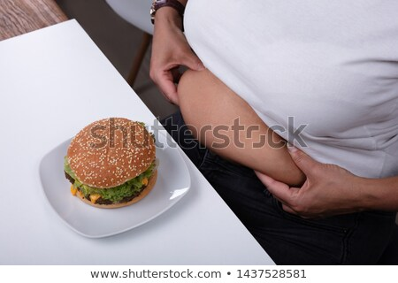 Overweight Woman Pinching Her Stomach With Hamburger On Table Stock photo © AndreyPopov