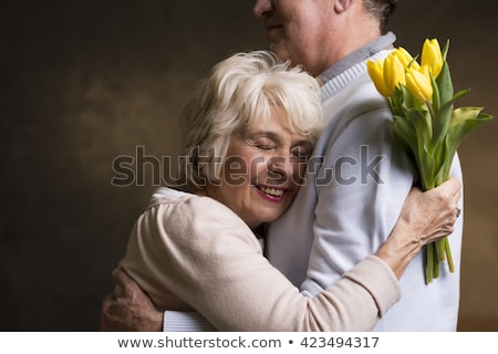 happy couple with bunch of flowers hugging at home Stock photo © dolgachov