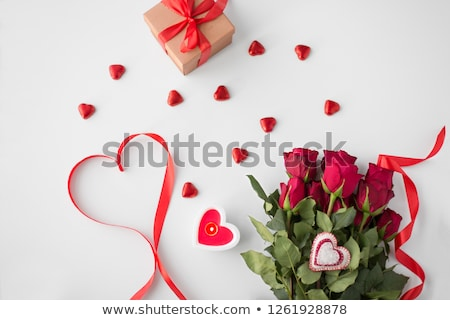 close up of red roses gift candies and candle stock photo © dolgachov