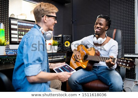 Happy African man with guitar and his colleague working over new soundtrack Stock photo © pressmaster