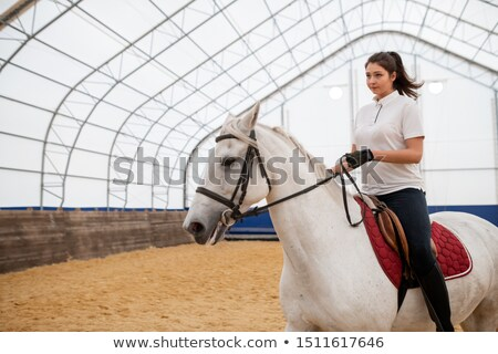 Serious young active woman looking straight while riding white purebred horse Stock photo © pressmaster
