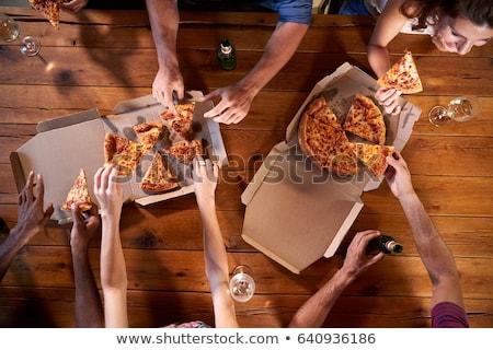 Znajomych jedzenie pizza pitnej wina domu Zdjęcia stock © dolgachov