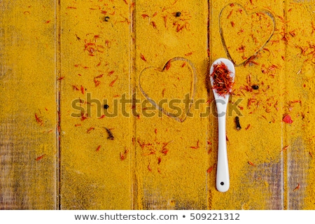 Heart of spices and seasonings. White spoon with saffron on curry background.  Various spices select Stock photo © Illia