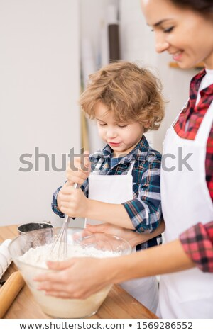 Female and her son in aprons whisking eggs with flour while preparing dough Stock photo © pressmaster