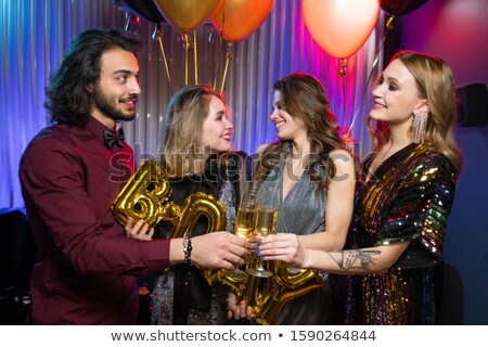 Happy young man clinking flute of champagne with one of girls at birthday party Stock photo © pressmaster