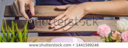 Young woman makes manicure with gel polish and UV lamp in pink shades BANNER, LONG FORMAT Stock photo © galitskaya