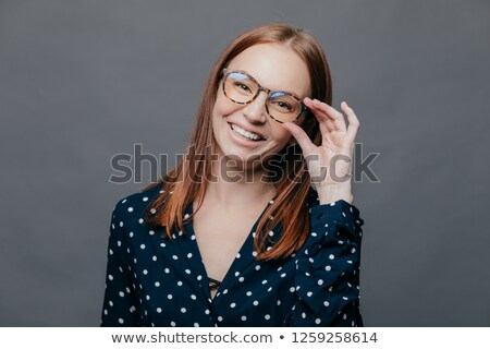 Smiling woman with pleased facial expression, keeps hand on rim of spectacles, wears black polka dot Stock photo © vkstudio