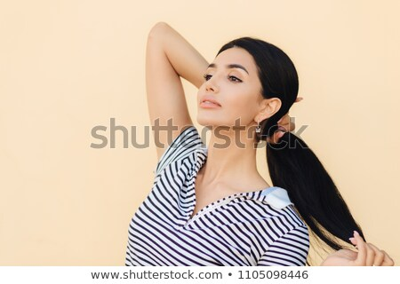 Sideways shot of good looking brunette woman keeps hair in pony tail, looks confidently into distanc Stock photo © vkstudio