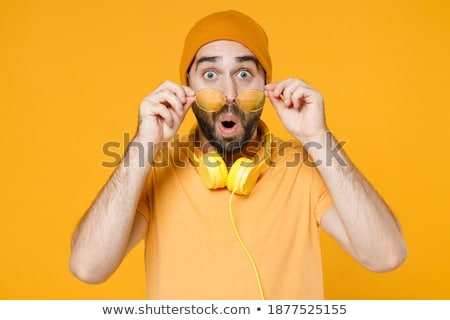 Image of young bearded man wearing basic white t-shirt looking at camera Stock photo © deandrobot