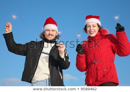 couple against blue sky background in winter in santa claus hats with sparklers stock photo © paha_l