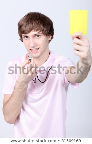 Young man holding up a yellow card and blowing his whistle Stock photo © photography33