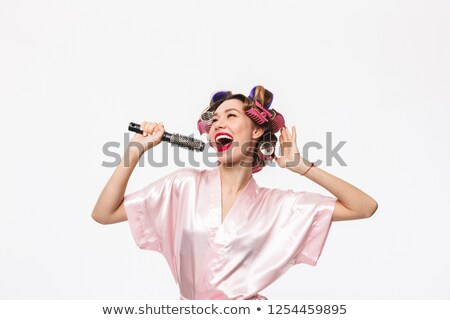 Woman wearing hair rollers, singing into brush Stock photo © photography33