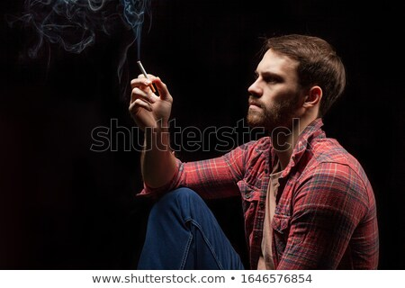 Stock photo: Young  man with a cigarette. Isolated on black