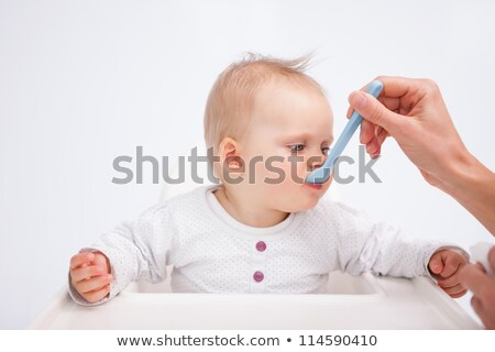 Cute baby eating while being accompanied by her mother against a grey background Stock photo © wavebreak_media