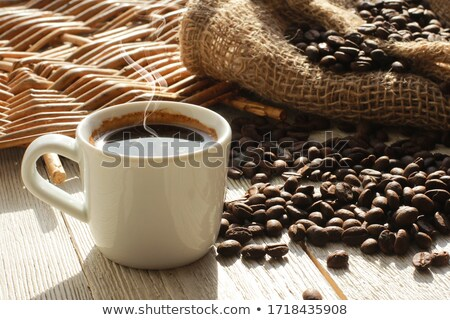 Stockfoto: Steaming Coffee Cup With Coffee Beans On A Jute Fabric