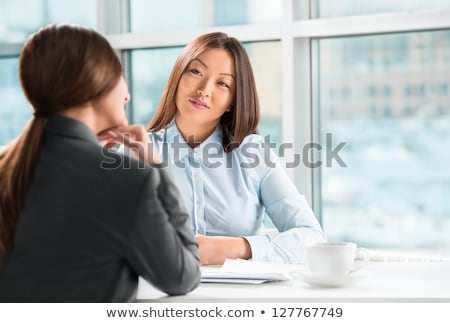 Two business women talking and signing contract at office Stock photo © HASLOO
