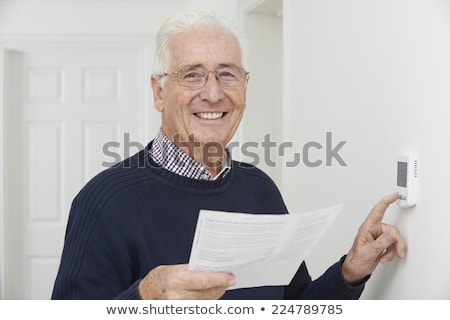 smiling senior man with bill adjusting central heating thermosta stock photo © highwaystarz