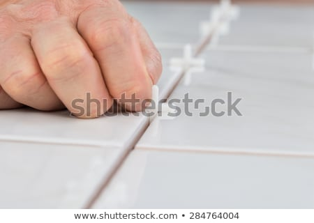 Person's Hand Placing Spacers Between Tiles Stock photo © AndreyPopov