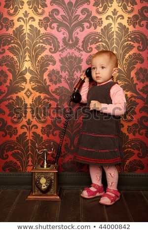 Standing little girl speaking on retro phone. Interior in retro style. Vertical format. Stock photo © Paha_L