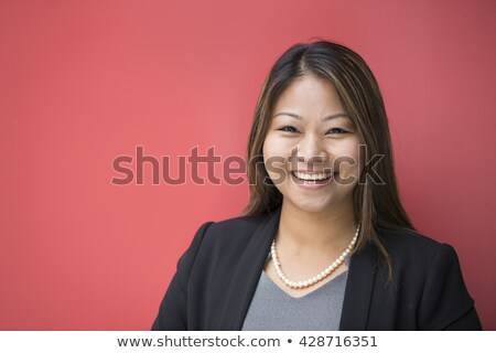 Stock photo: Thoughtful businesswoman facing and leaning against a wall