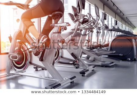 attractive woman athlete riding on bicycle in gym stock photo © deandrobot