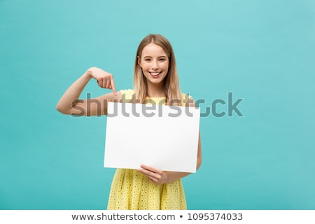 pretty young woman holding empty blank board over blue background stock photo © deandrobot
