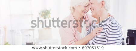 senior couple kissing in kitchen stock photo © is2