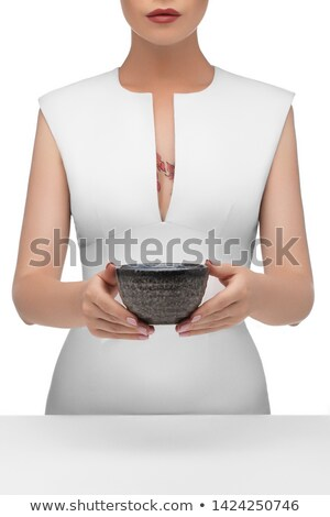 A girl with a tattoo on her hands holding a flowers on a gray. Stock photo © artjazz
