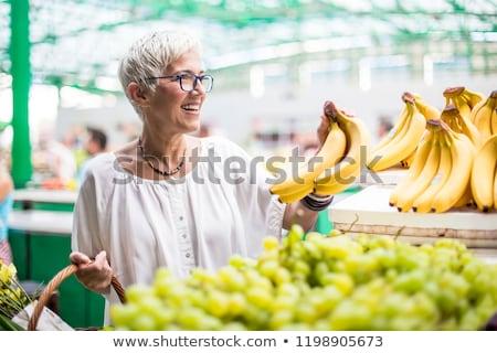 Good-looking senior woman buys bananas at the market Stock photo © boggy
