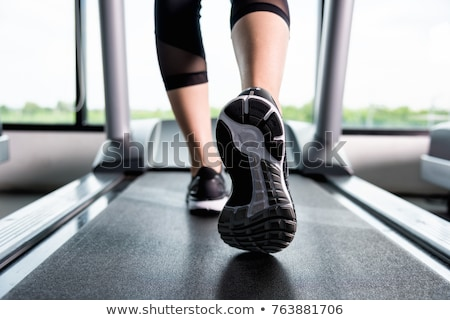 Fit active woman running on treadmill during workout Stock photo © Kzenon