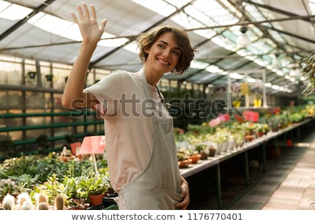 Emotional cute woman gardener standing over flowers plants in greenhouse waving Stock photo © deandrobot