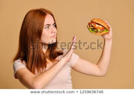 Mujer sonriente mirando Burger sonriendo pie Foto stock © AndreyPopov