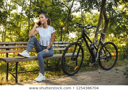 Image of european woman sitting on bench in park with bicycle, a Stock photo © deandrobot