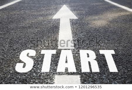 Közelkép nyíl szó kezdet aszfalt út Stock fotó © dolgachov
