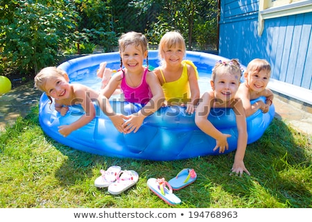 Smiling Girl Playing In The Inflatable Pool On Beach Stock photo © AndreyPopov