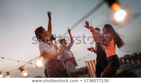 happy couple with drinks at rooftop party Stock photo © dolgachov