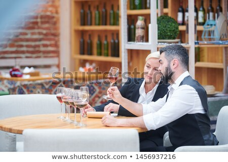 Young man showing his colleague sample of new sort of wine in wineglass Stock photo © pressmaster
