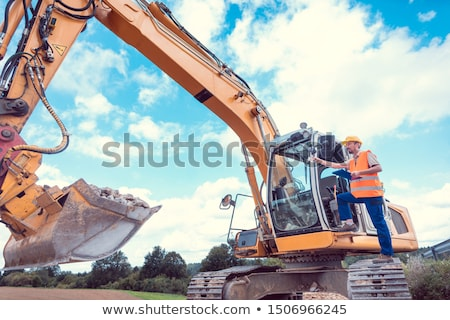Stock photo: Construction Worker On Excavator Planning The Work To Be Done