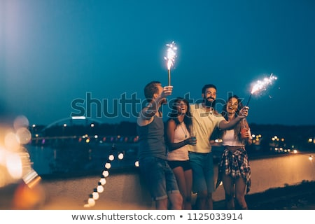 happy friends with sparklers at rooftop party Stock photo © dolgachov