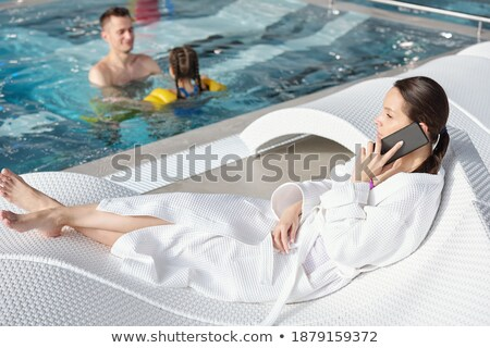 Adult ethnic woman in swimwear resting at poolside Stock photo © dash